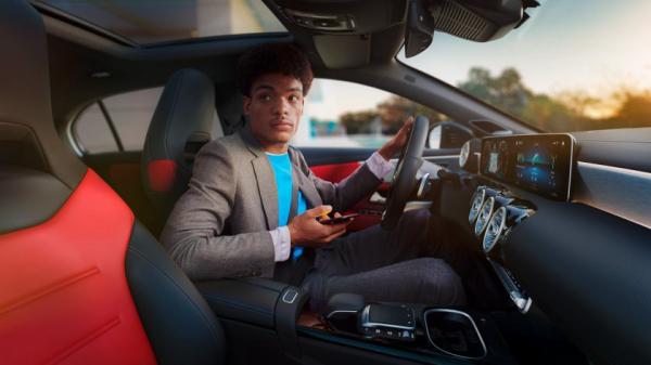 A man sitting inside a Mercedes-Benz A class hatchback
